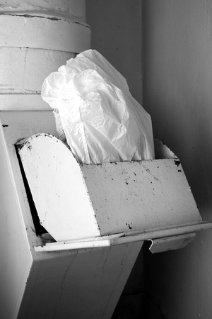 A jammed cellophane bag stuck in disposal bin, vertical image in black and white