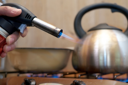 gas lighter: A gas lighter in a male hand and a stove top with kettle on it, closeup shot