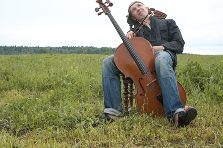 cellos: Musician with a happy look on his face having a break while performing a cello in a field landscape