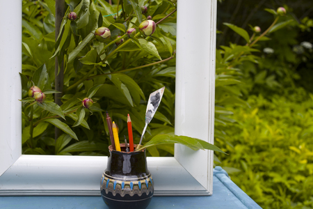 Picture frame, peony flowers and vase with artist equipment on the garden table. Concept of leisure activities