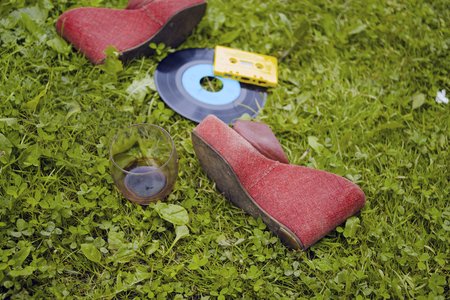 Red high heels, red wine glass and compact cassette spread out on the grass, concept of party is over Stock Photo