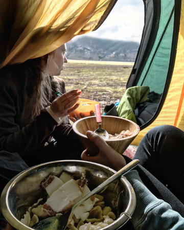 Young females having breakfast in tourist tent, a beautiful mountains landscape in the background