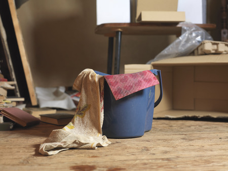 Cleaner basket with cloth and water in the foreground and messy room in the background