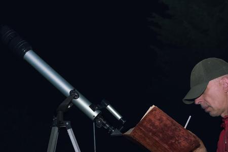 Hombre haciendo dibujo o dibujo con un libro en las manos, sentado al lado de un telescopio aficionado Foto de archivo