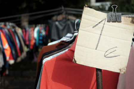 One euro price tag attached to the clothes hanging on the hangers Stock Photo