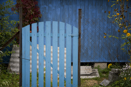 A closed wooden gate in focus and abandoned house or barn in the background