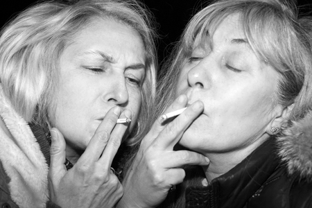 Night scene with two women smoking joints or cigarettes, in black and white