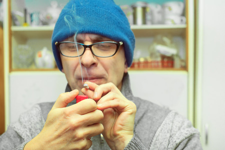 Man wearing glasses lighting a joint or cigarette in the kitchen, indoor filtered shot Stock Photo