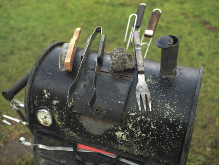 A barbecue trolley with metal brush, tongs and grill bars in the green lawn