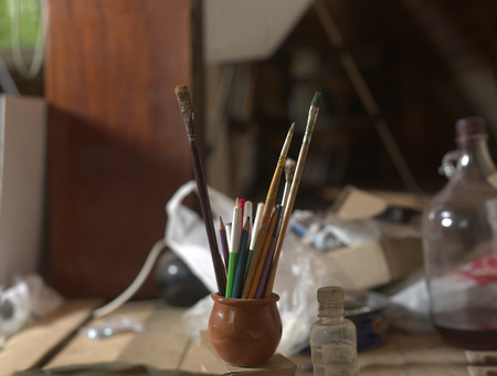 Mess in a loft with bunch of paint brushes in focus, indoor closeup Stock Photo