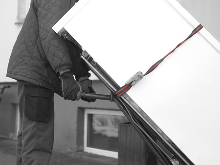 A man moving a brand new refrigerator loaded on trolley, selective color shot