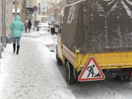 Rear of a truck with Works Ahead sign on a street covered with snow Stock Photo