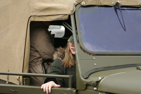 A girl about to open a door of a military vehicle with tarpaulin top