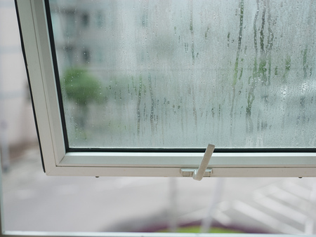 Closeup of an open window with water drops in a rainy day