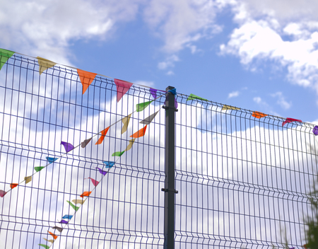 Colorful festive flags on a metal fence against the blue sky,