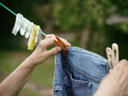 Aged female hands pinning washed clothes on a rope, outside closeup