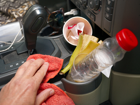 A male hand cleaning car interior full of rubbish
