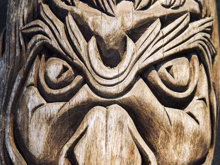 Aggressive looking wooden carved face, closeup filtered shot Stock Photo