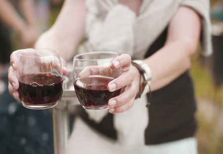 Filtered image of female hands offering two glasses of wine