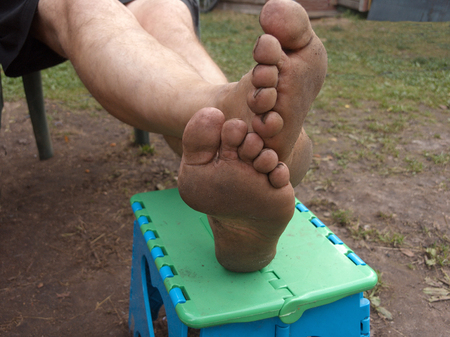 Man relaxing outdoors with dirty feet, selective focus closeup