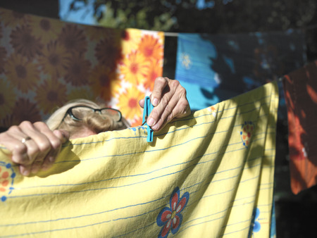 Outdoor closeup of female hands pinning washed laundry on a rope Stock Photo