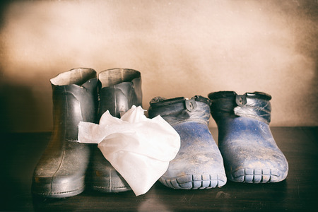 Filtered shot of the dirty waterproof rubber boots and cleaning tissue