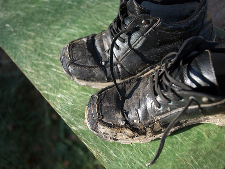 A pair of leather men shoes covered with sticky mud drying outdoors