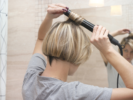 Young female curling hair with a hair styler, looking at the mirror, indoor close-up Stock Photo