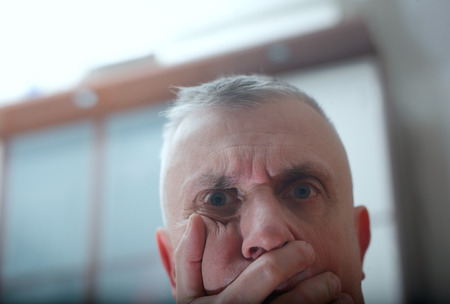 Cropped portrait of a shocked man covering face, studio shot Stock Photo