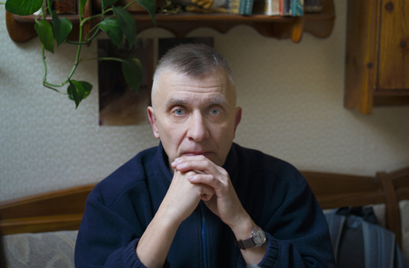 A serious looking man posing with a straight gaze, indoor cropped portrait