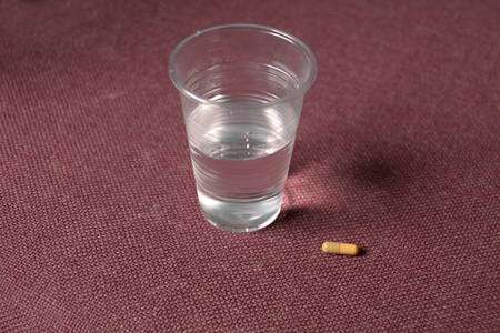 Pill And Glass Of Water On Red