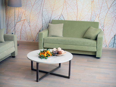 Clean modern livivg room with a table in the center, decorated with fruits