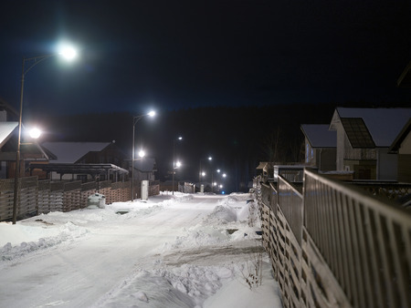 Snowy street with small houses behing the fences and night illumination, winter scene