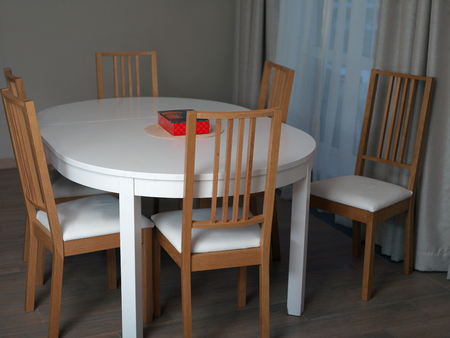 A dinner table with a red box on the top and wooden chairs, indoor shot