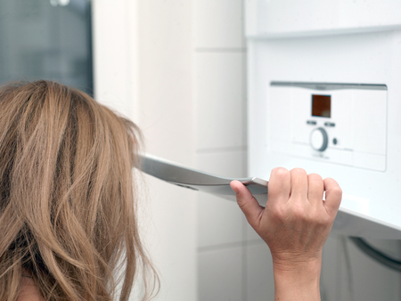 Close-up of a woman with long hair about to set temperature on a gas boiler, indoor shot with selective focus