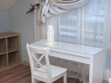 White table and room in front of the window with a half shut curtain