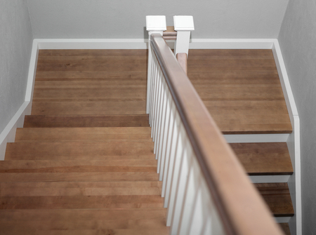 A wooden staircase leading up and down, cropped interior shot Stock Photo