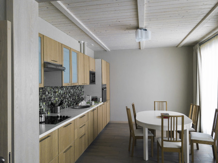 A modern kitchen interior with dinner table in the center Stock Photo