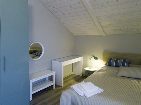 A bed with towels on a the blanket in a bedroom with wooden ceiling