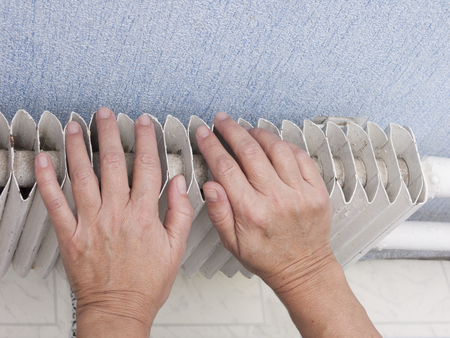 Close-up of a woman warming her hands near a hot radiator Stock Photo