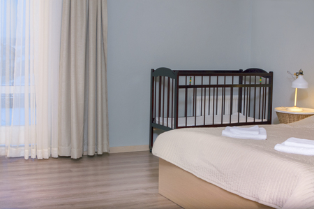 Baby bed cradle behind the parents bed, interior shot Stock Photo