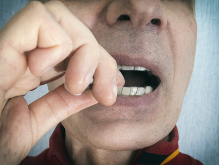 Close-up of a man removing food stuck between the teeth, filtered portrait Stock Photo