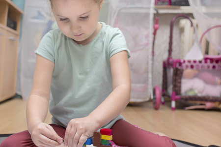A little girl of four years old sitting on a floor playing on her own in a playroom