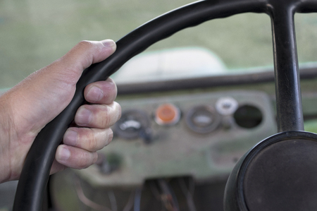 A diver hand close-up gripping a retro steering wheel, selective focus close-up