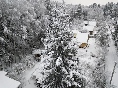 Aerial view of a small village lost in the forest during a snowfsll Stock Photo