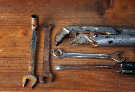 Set of old rusty wrenches laid on the wooden surface