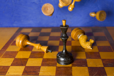 A king in a center of chessboard and pieces falling down in the blurred background, concept of success