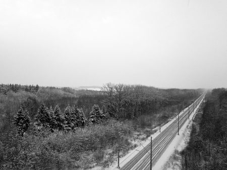 Panoramic aerial view of a railroad going through the snowy fields and forests, in black and white