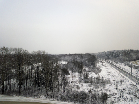 Panoramic aerial view of a railroad going through the snowy fields and forests