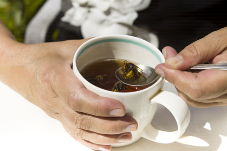 A woman taking wasp out of tea cup, outdoor close-up
